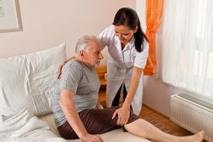 home health care worker aiding senior out of bed